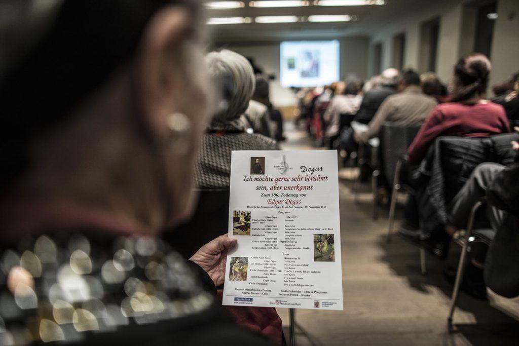 Degas, Publikum liest in Informationsblatt zur Veranstaltung